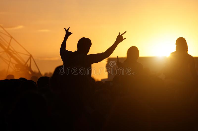 Silhouette Concert Person, Man on Shoulders in Crowd with hands up at summer Music Festival royalty free stock images