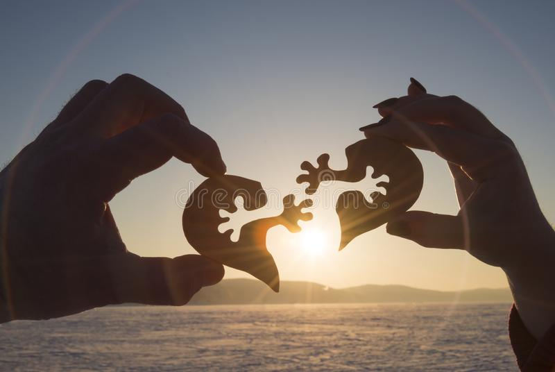 Silhouette connect heart two pieces of puzzle in hands of lovers against the background of sunrise. stock photo