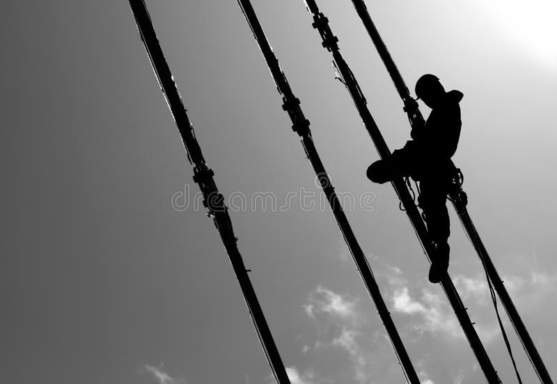 Silhouette of construction climber. On suspension bridge royalty free stock image