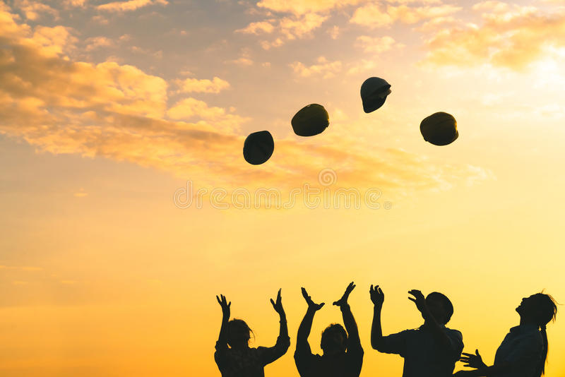 Silhouette of construction engineers throw safety helmet upward on sunset sky, engineering industry or success teamwork celebrate stock photography