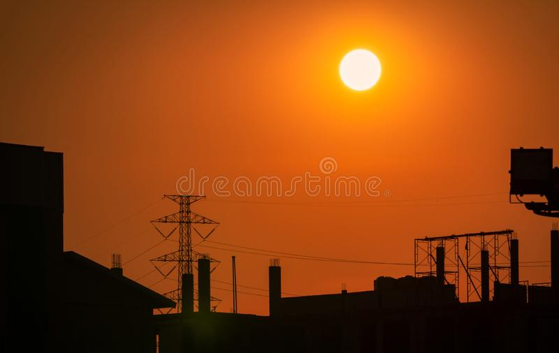 Silhouette construction site with orange sunset sky background. High voltage electric tower. Beautiful big sun at sunset stock photo
