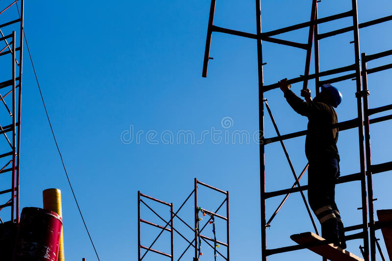 Silhouette of construction worker against sky on scaffolding wit. H ladder on building site stock images