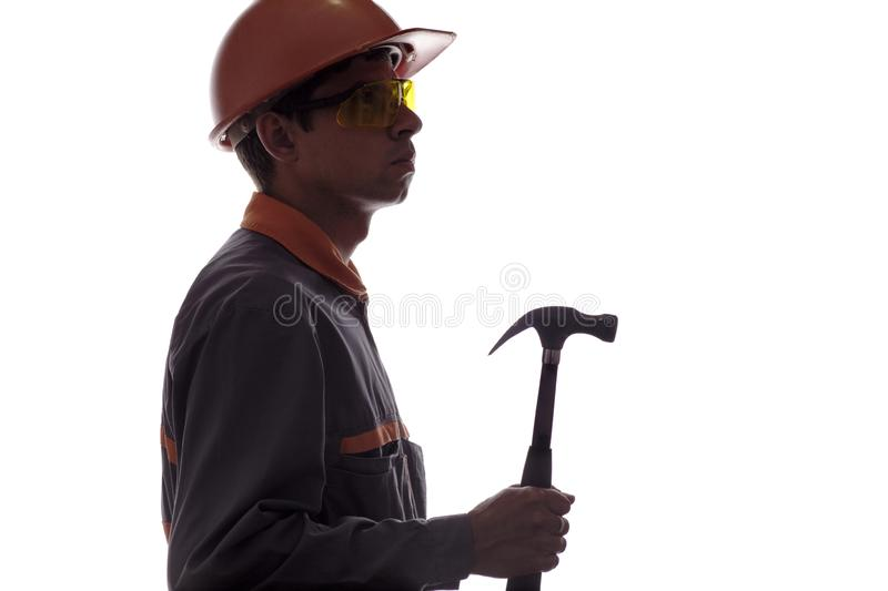 Silhouette of construction worker with hammer, man in hard hat and goggles in construction robe on white isolated background royalty free stock images