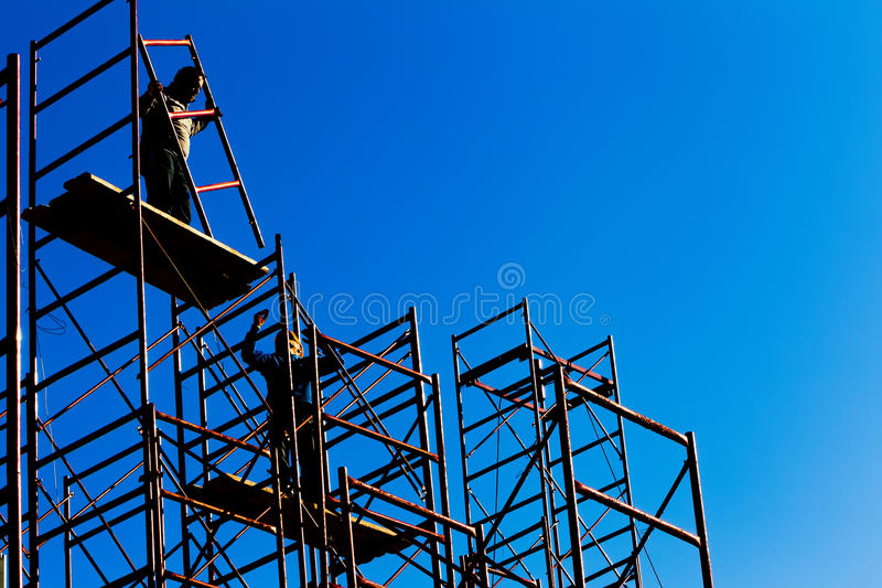 Silhouette of construction workers against sky on scaffolding wi royalty free stock images