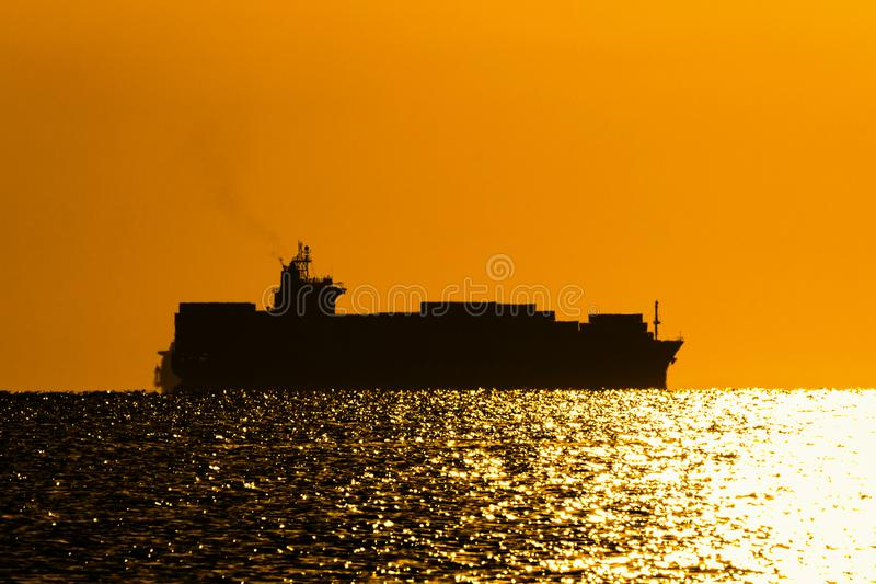 Silhouette of a container ship on the background of the morning sky stock image