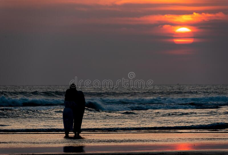 Silhouette of a couple on the beach at sunset. In bali stock image