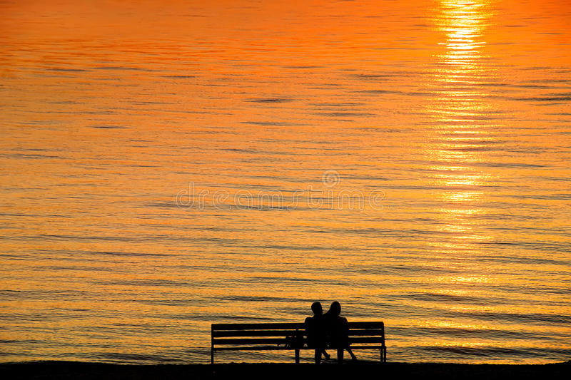 Silhouette of a couple on a bench at sunset against romantic ora. Nge colored sea. Summer leisure, vacation and romance theme stock images