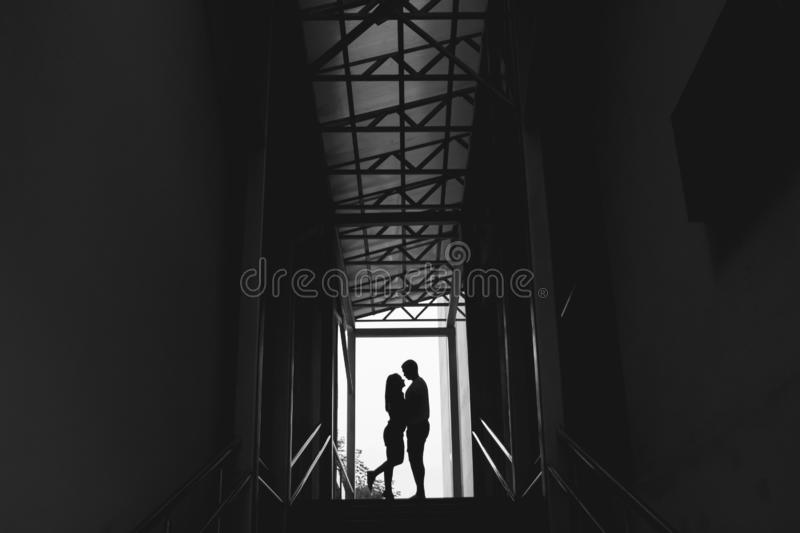 Silhouette of a couple on bright background at the end of an underground pedestrian tunnel stock photos