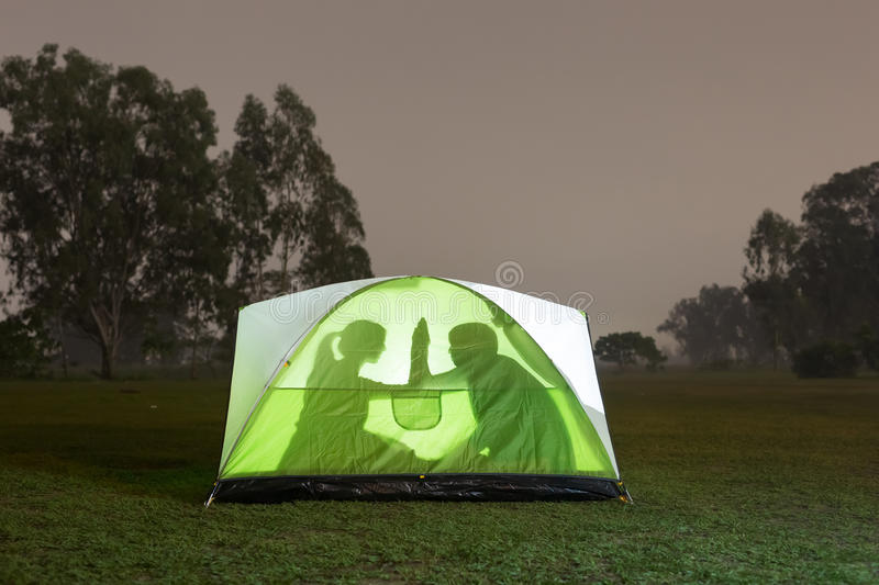 Silhouette of couple camping stock photo