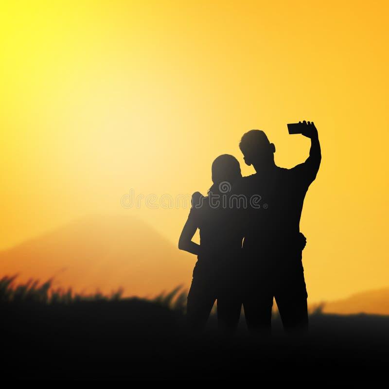 Silhouette couple do selfie stock image