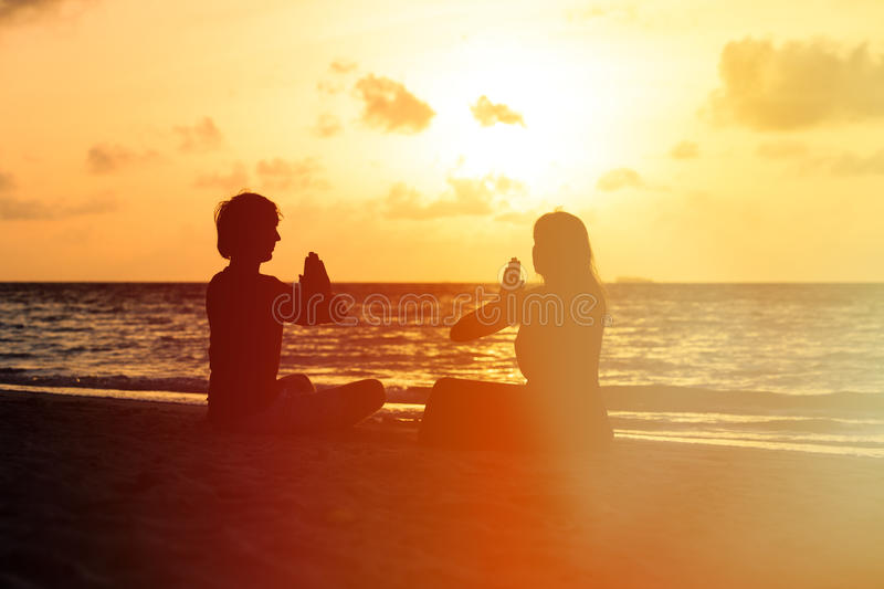 Silhouette of couple doing yoga at sunset stock images
