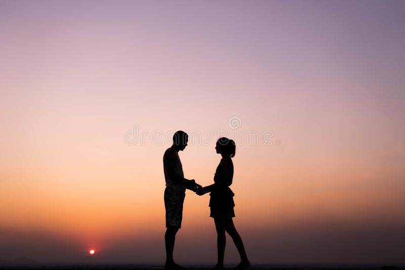 Silhouette of couple holding hand at sunset royalty free stock photography