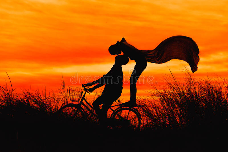 Silhouette couple kissing on bike royalty free stock image