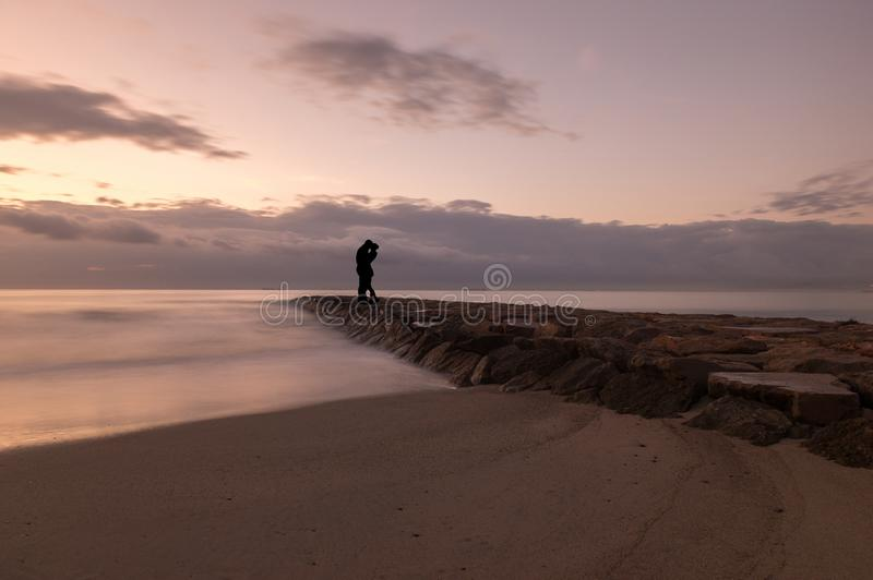 Silhouette of a couple kissing by the sea at sunrise royalty free stock image