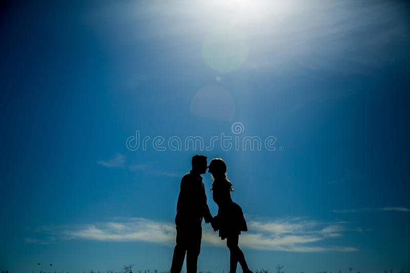 Silhouette of a couple leaning over to kiss royalty free stock image