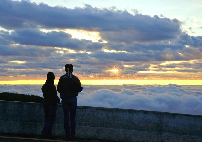 Silhouette couple looking at the beautiful sunrise on the top of. Mountain with the view into misty valley. Morning mountain landscape with wave of fog, Doi royalty free stock images