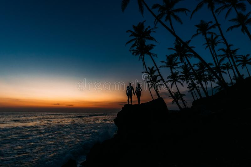 Silhouette of a couple in love on the beach. Man and woman at sunset. Honeymoon on the Islands. Man and woman meet sunset. Happy stock image