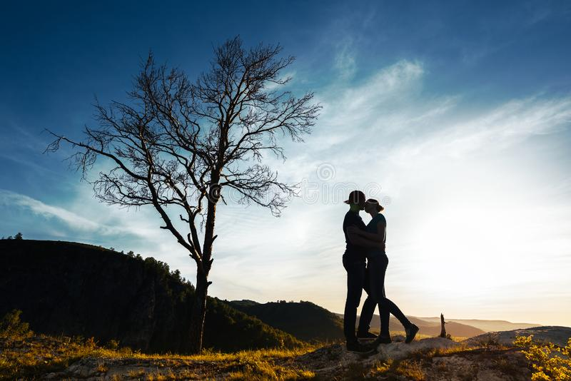 Silhouette of a couple in love. Guy and girl hugging at sunset. Couple travels. Lovers in nature. Man and woman watching the stock image