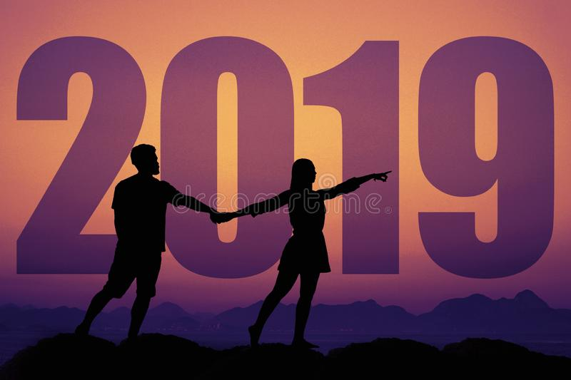 Silhouette of a couple in love at sunset with new year 2019 stock photos