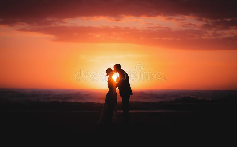 silhouette of couple lovers, bride and groom holding hands during sunrise time at the beach with beautiful pink sunrise sky. royalty free stock image