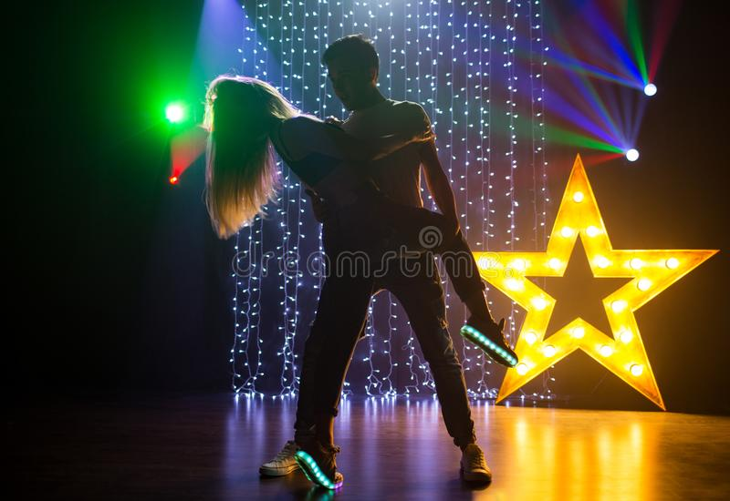 Silhouette couple of loving young man and woman dancing and having fun in a nightclub. Silhouette couple of loving young men and women dancing and having fun in royalty free stock photography