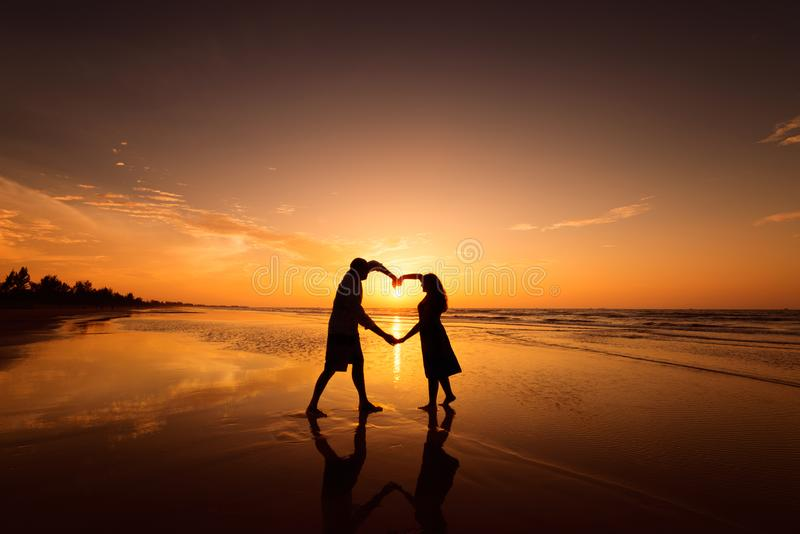 Silhouette of couple making heart shape with arms on beach at sunset royalty free stock photo