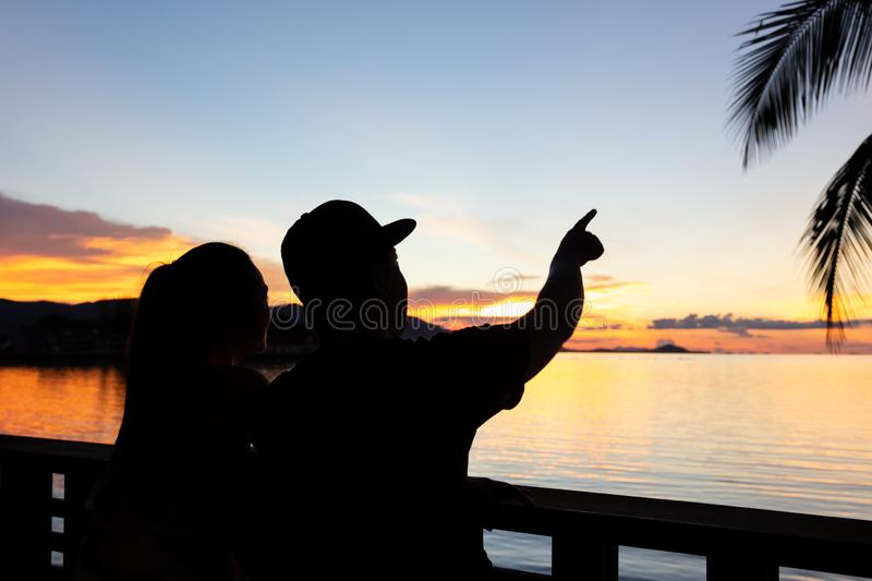 Silhouette couple man hand pointing out in sky at sunset over th royalty free stock photos