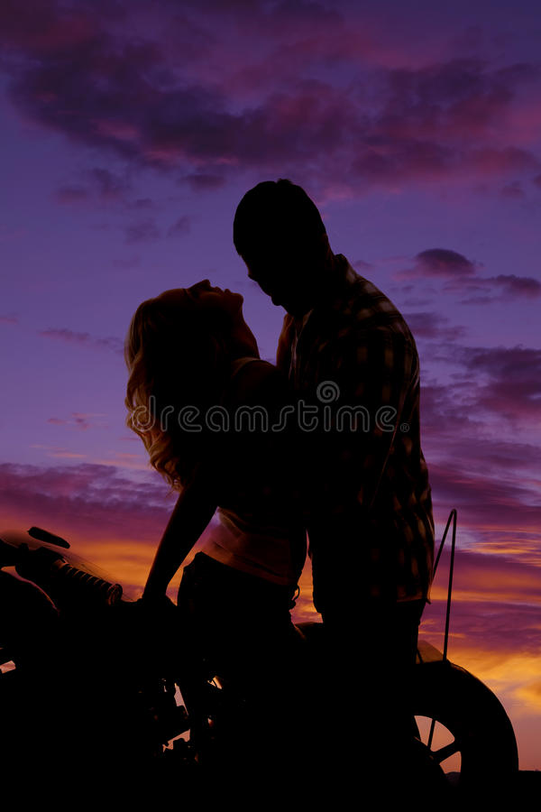 Silhouette couple on motorcycle her head back royalty free stock photography