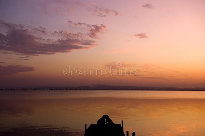 Silhouette of a couple on pier stock photo
