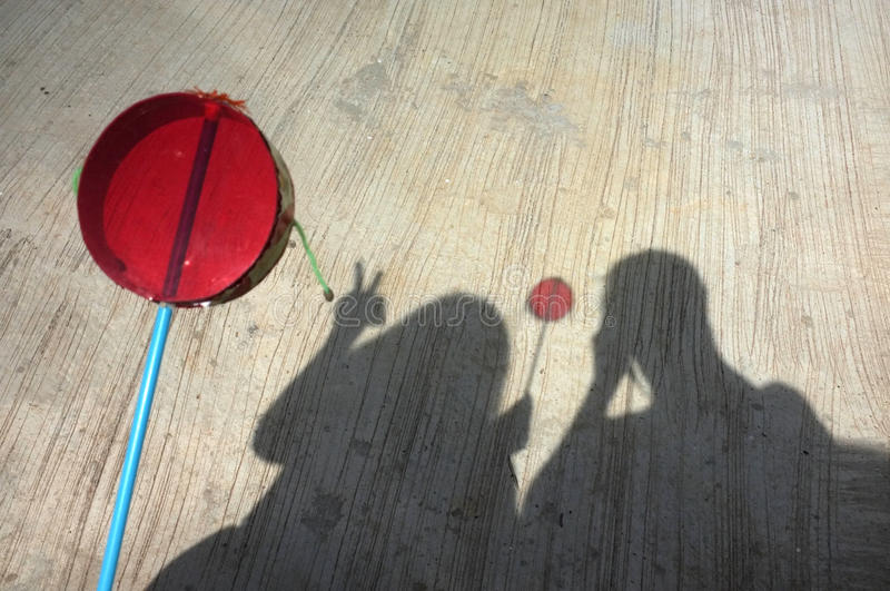 Silhouette of couple playing asian hand drum toy. On street stock photos