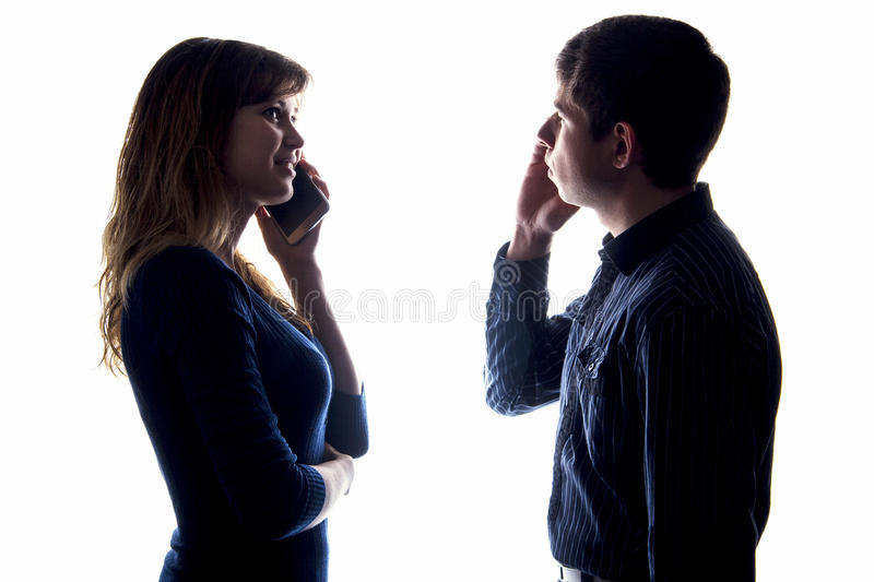 Silhouette of a couple with a problem in relationships. Silhouette of a young couple with a problem in relationships: everyone spends time in social networks or stock photos