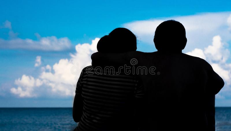 Silhouette of a couple on the sea royalty free stock photo
