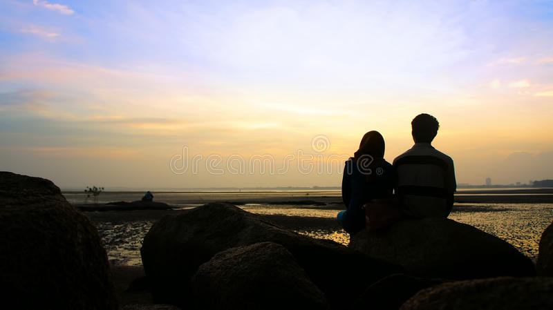 Silhouette of couple sitting on the rock looking at the sun. Goes down royalty free stock photos