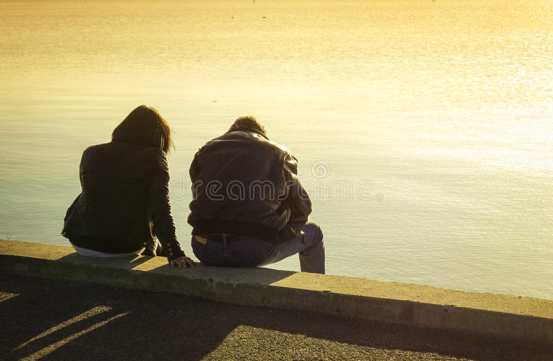 Silhouette of a couple sitting at the seaside royalty free stock photos