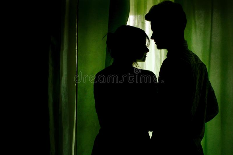 silhouette of couple standing at green curtains at window and hugging royalty free stock images