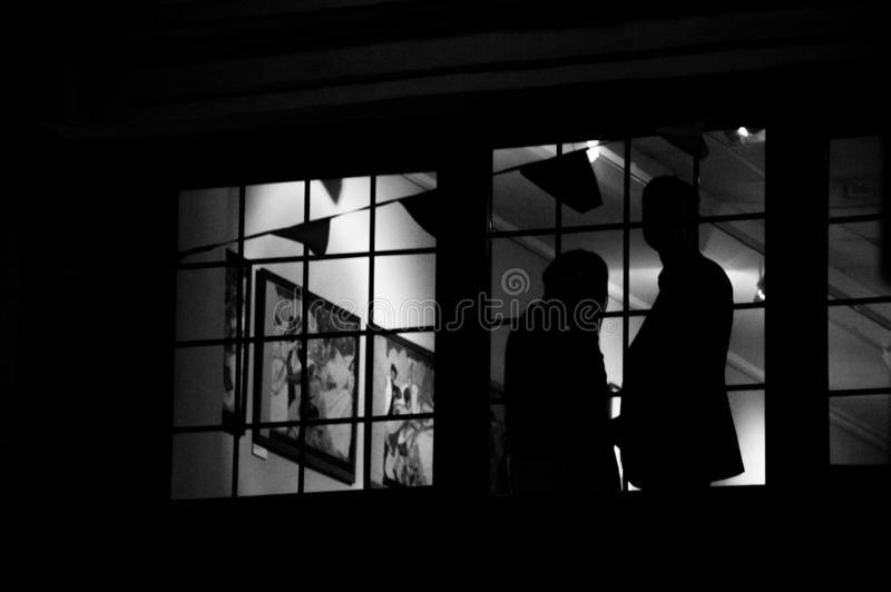Silhouette of a couple standing and looking through big window at tree crown branches background stock photo