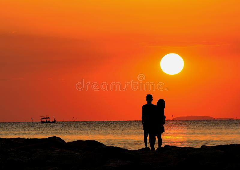 Silhouette of couple standing by the sea watching the sunset. stock images