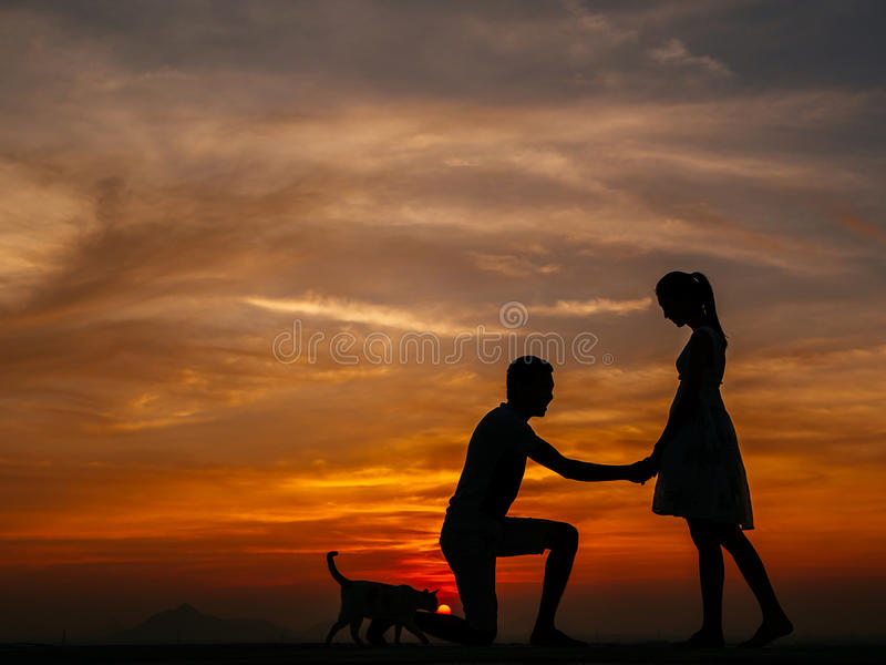 Silhouette of Couple at Sunset. Silhouette of Happy Young Couple Hugging Outside at Sunset,proposing royalty free stock photography