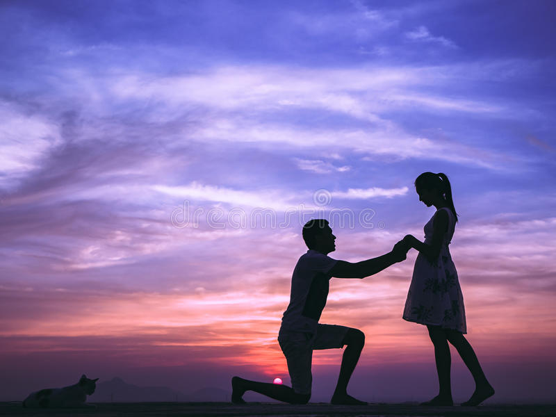 Silhouette of Couple at Sunset. Silhouette of Happy Young Couple Hugging Outside at Sunset,proposing royalty free stock image