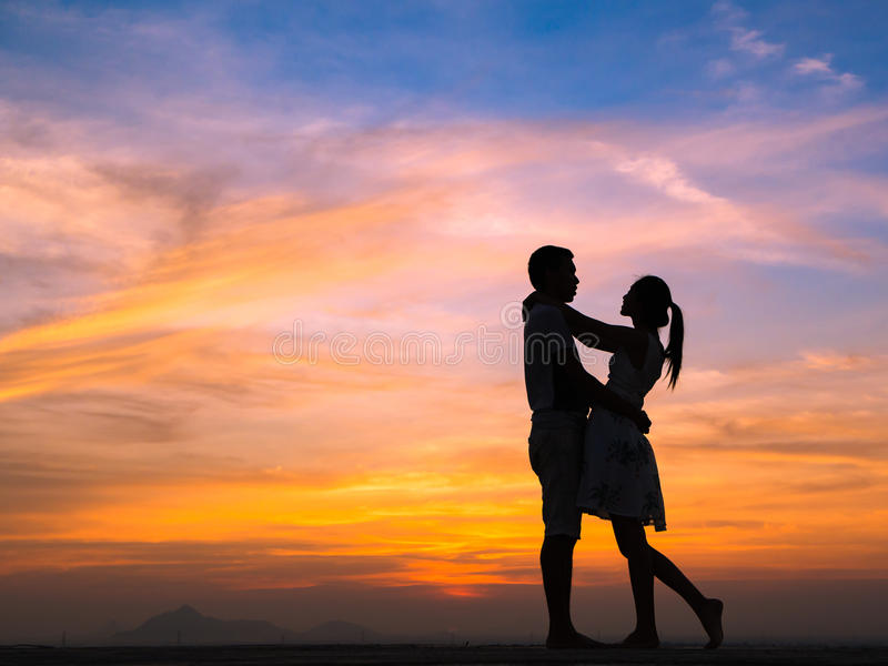 Silhouette of Couple at Sunset. Silhouette of Happy Young Couple love Outside at Sunset royalty free stock photo