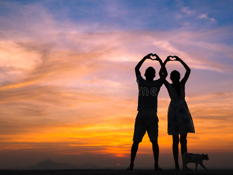 Silhouette of Couple at Sunset. Loving couple showing heart symbol on hands,twilight background royalty free stock photography
