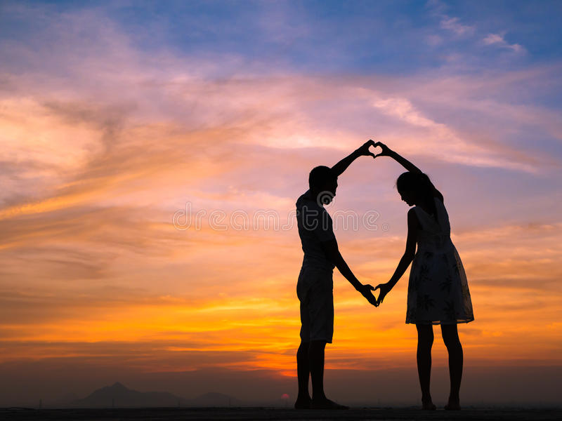 Silhouette of Couple at Sunset. Loving couple showing heart symbol on hands,twilight background royalty free stock image