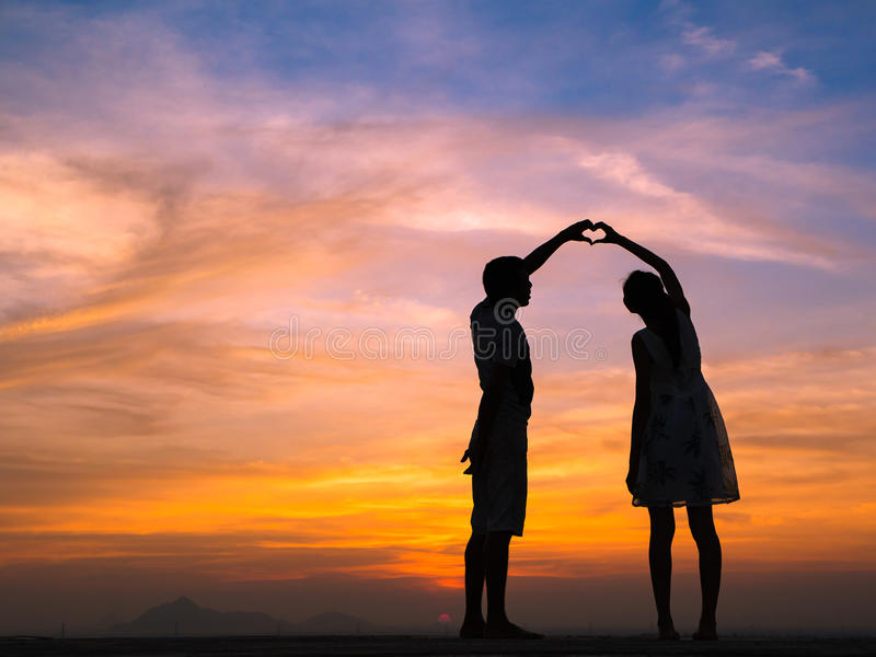 Silhouette of Couple at Sunset. Loving couple showing heart symbol on hands,twilight background stock images
