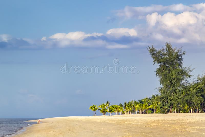Silhouette of a couple walking along a deserted tropical beach against the sunset sky with clouds stock photos