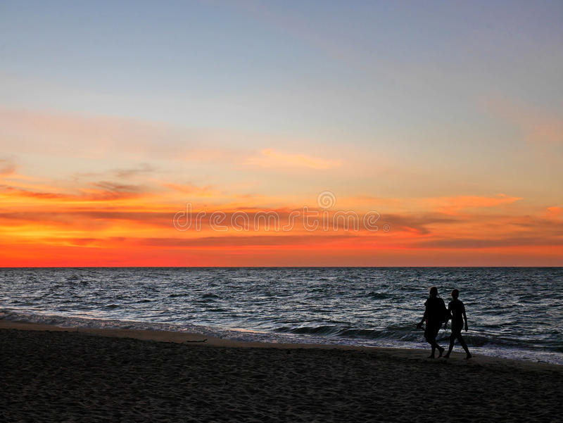 Silhouette couples walking along sunset beach royalty free stock images