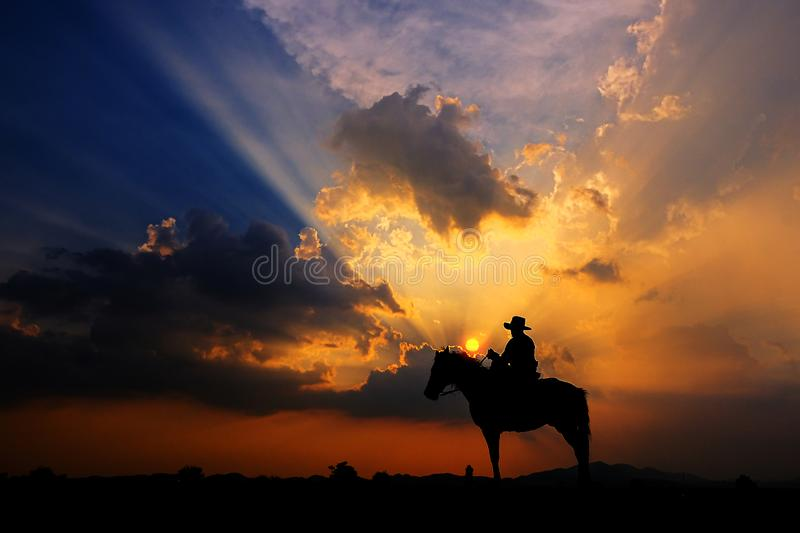 The silhouette of a cowboy on horseback at sunset on  background. The silhouette of a cowboy on horseback at sunset on a  background stock photos
