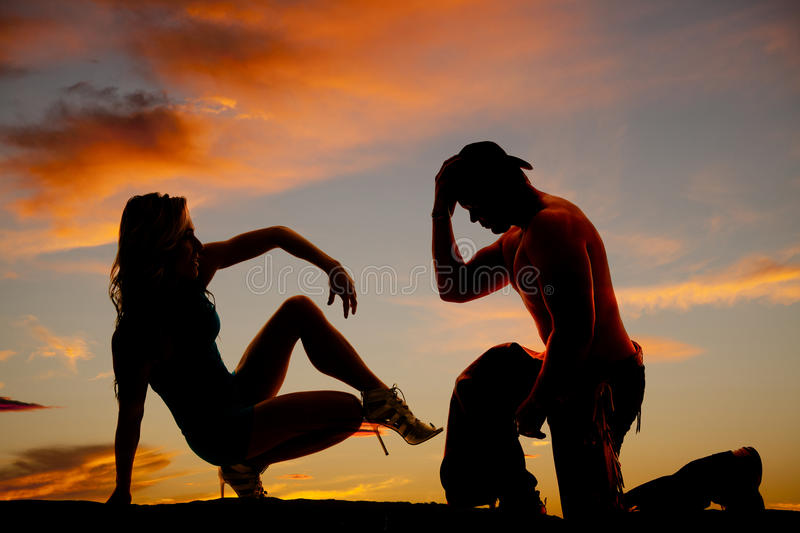 Silhouette of cowboy on knee and woman sit back one leg up in th stock photography