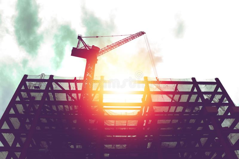 Silhouette of crane in building construction site stock images