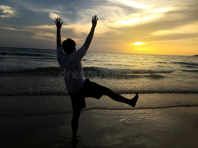 Silhouette of crazy funny happy man gesture on a beach when sunrise stock image