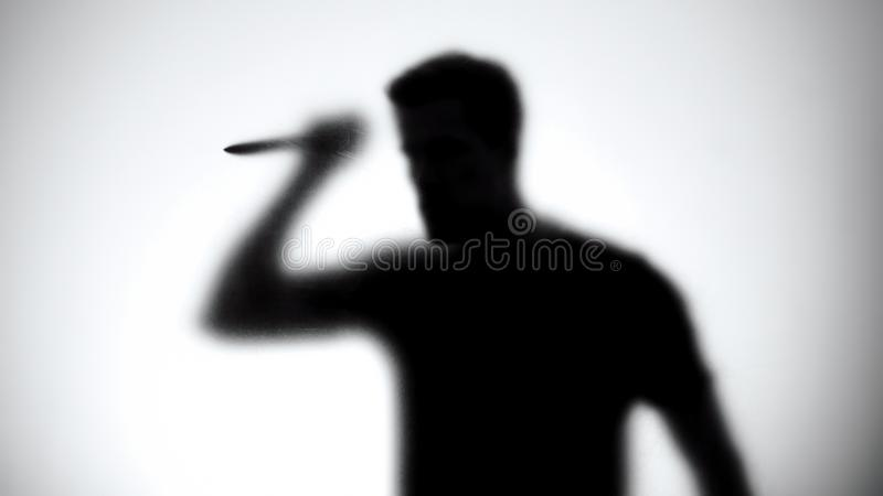 Silhouette of crazy maniac with knife standing behind glass wall, thriller royalty free stock photo